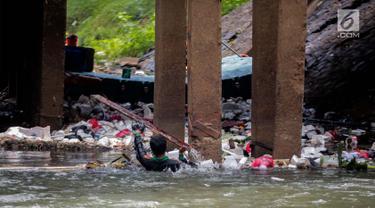 Aksi petugas PPSU bersihkan sampah yang tersangkut ditengah deras arus aliran anak kali Ciliwung, Jakarta, Senin (22/7/2019). Pembersihan sungai dari berbagai sampah tersebut dimaksudkan agar tidak ada penumpukan sampah dan sedimentasi saluran di sepanjang sungai. (Liputan6.com/Faizal Fanani)