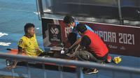 Anggota satgas COVID-19 itu adalah Nanang Tri Wahyudi ikut membantu penangangan cedera pemain Barito Putera, Bagas Kaffa di Stadion Kanjuruhan, Sabtu (10/4/2021). (Bola.com/Iwan Setiawan)