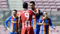 Striker Atletico Madrid, Luis Suarez, berbincang dengan gelandang Barcelona, Sergio Busquets, pada laga Liga Spanyol di Stadion Camp Nou, Sabtu (8/5/2021). Kedua tim bermain imbang 0-0. (AFP/Josep Lago)