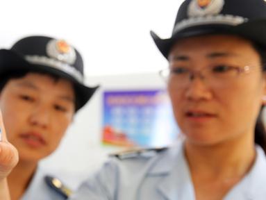 Petugas BPOM China memeriksa vaksin rabies di Pusat Pengendalian dan Pencegahan Penyakit di Huaibei, provinsi Anhui, Selasa (24/7). Otoritas China menginvestigasi skandal produksi vaksin rabies ilegal yang telah menimbulkan kepanikan masyarakat. (AFP)
