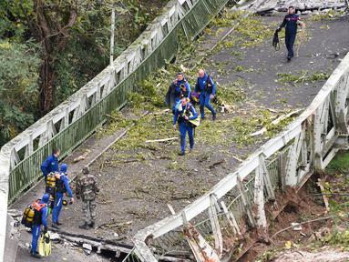Tim penyelamat berjalan di atas jembatan gantung yang ambruk di atas sungai Tarm, Prancis, Selasa (18/11/2019). Jembatan gantung yang menghubungkan kota Mirepoix-sur-Tarn itu tiba-tiba ambruk hingga menyebabkan seorang gadis berusia 15 tahun dan satu sopir truk tewas. (ERIC CABANIS/AFP)