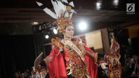Finalis Kalimantan Timur, Amel Barack menampilkan bakat dalam balutan busana tradisional dari daerahnya saat babak preliminary Miss Grand Indonesia 2018 di Jakarta, Senin (16/7). Sebanyak 30 finalis mencapai babak preliminary (Liputan6.com/Faizal Fanani)