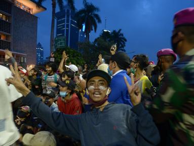 Sejumlah pendemo foto bersama dengan anggota Marinir saat aksi menolak Omnibus Law UU Cipta Kerja di kawasan Patung Kuda, Jakarta, Selasa (20/10/2020).  Anggota Marinir membubarkan dan mengawal pulang massa pendemo  ke rumah masing-masing. (merdeka.com/Imam Buhori)