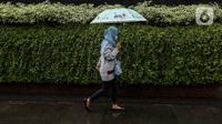 Seorang warga menggunakan payung saat hujan di kawasan Jakarta, Selasa (16/2/2021). Sebagai tahap awal vaksinasi COVID-19 tahap kedua bagi pekerja publik akan dimulai dari para pedagang Pasar Tanah Abang pada Rabu 17 Februari 2021. (Liputan6.com/Johan Tallo)