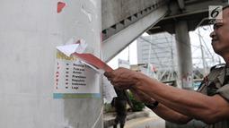 Petugas Satpol PP mencopot poster yang terpasang di JPO saat penertiban APK di sepanjang Jalan Yos Sudarso, Jakarta Utara, Rabu (13/3). APK yang dipasang di sembarang tempat dan fasilitas umum melanggar SK KPU nomor 175. (merdeka.com/Iqbal S. Nugroho)