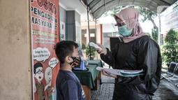 Petugas paramedis memeriksa suhu tubuh salah seorang anak sebelum mengikuti program BIAS di Kantor Kelurahan Tamansari, Jakarta, Selasa (24/11/2020). BIAS dilakukan dengan konsisten menerapkan protokol kesehatan COVID-19. (merdeka.com/Iqbal S. Nugroho)