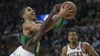 Pemain Boston Celtics, Jayson Tatum mencoba lewati adangan pemain Milwaukee Bucks, Tony Snell pada laga NBA di basketball game di Milwaukee, (26/10/2017). Boston menang 96-89. (AP/Tom Lynn)