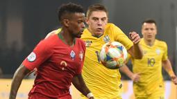 Bek Portugal, Nelson Semedo, berusaha melewati bek Ukraina, Vitaliy Mykolenko, pada laga Kualifikasi Piala Eropa 2020 di Stadion NSK Olimpiyskyi, Kiev, Senin (14/10). Ukraina menang 2-1 atas Portugal. (AFP/Genya Savilov)
