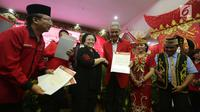 Ketum PDIP Megawati Soekarnoputri memberi surat mandat calon gubernur di Pilkada Jawa Tengah 2018, Ganjar Pranowo saat pengumuman cagub-cawagub PDIP di kantor DPP PDIP Lenteng Agung, Jakarta, Minggu (7/1). (Liputan6.com/Faizal Fanani)