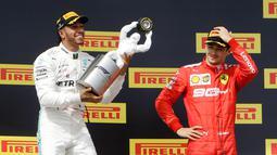 Pebalap Mercedes Lewis Hamilton (kiri) memegang trofi juara disaksikan pebalap Ferrari Charles Leclerc setelah menjuarai F1 GP Prancis 2019 di Sirkuit Paul Ricard, Minggu (23/6/2019). Hamilton tampil dominan dan menjadi juara F1 GP Prancis 2019. (AP Photo/Claude Paris)