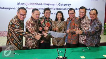 Menteri BUMN Rini Soemarno (tengah) bersama Gubernur BI Agus Martowardojo dan sejumlah Dirut Bank BUMN tengah memegang naskah MoU sinergi pembentukan perusahaan prinsipal di Jakarta, Jumat (9/9). (Liputan6.com/Angga Yuniar)