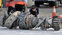 Petugas Komisi Nasional Keselamatan Transportasi (KNKT) memeriksa turbin pesawat Lion Air PK-LQP JT610 di posko evakuasi JICT 2, Tanjung Priok, Jakarta, Minggu (4/11). Mesin tersebut ditemukan di perairan Tanjung Karawang. (merdeka.com/Iqbal S. Nugroho)
