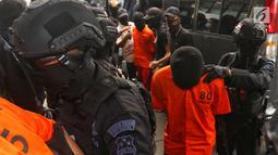 Polisi bersenjata lengkap mengawal sejumlah terduga teroris untuk dihadirkan dalam jumpa pers di Mabes Polri, Jakarta, Jumat (17/5/2019). Sepanjang bulan Mei 2019, tim Densus 88 Antiteror telah menangkap sebanyak 29 terduga teroris jaringan Jamaah Ansharut Daulah (JAD). (Liputan6.com/Johan Tallo)