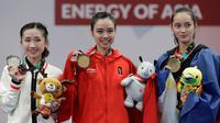 Atlet Wushu Indonesia, Lindswell Kwok (tengah) foto bersama denga atlet wushu Hongkong, Mok Uen Ying (kiri) dan atlet wushu Filipina Agatha Wong setelah pemberian medali pada Asian Games ke-18 di Jakarta, (20/8). (AP Photo/Aaron Favila)