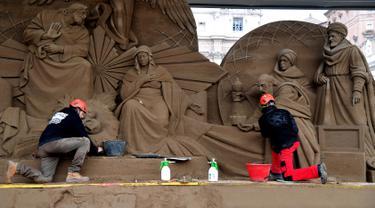 Seniman Rusia Ilya Filimontsev (kiri) dan seniman Ceko Radovan Zivny (kanan) saat membuat patung pasir adegan kelahiran Yesus di St Peter, Vatikan, Kamis (6/12). Patung ini dipersiapkan untuk menyambut Natal. (Tiziana FABI/AFP)