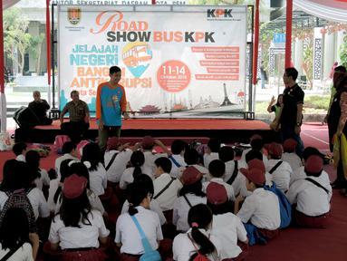 Sejumlah siswa SD mendengarkan dongeng antikorupsi saat Roadshow Bus KPK tiba di Balai Kota Semarang, Jawa Tengah, Sabtu (13/10). Langkah ini untuk mencegah korupsi sejak dini. (Liputan6.com/Gholib)