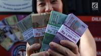 Seorang warga menunjukkan uang pecahan hasil penukaran di Lapangan IRTI Monas, Jakarta, Rabu (23/5). Bank Indonesia (BI) telah membuka layanan kas keliling bekerja sama dengan 13 bank di kawasan Monas. (Liputan6.com/Arya Manggala)
