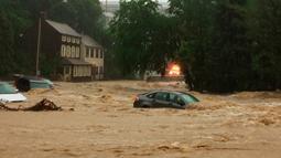 Sejumlah mobil terjebak dalam banjir yang menggenangi Ellicott City, Maryland (27/5). Akibat banjir ini jalan utama berubah layaknya sungai dan menyapu sejumlah mobil yang terparkir. (Kenneth K. Lam / The Baltimore Sun via AP)