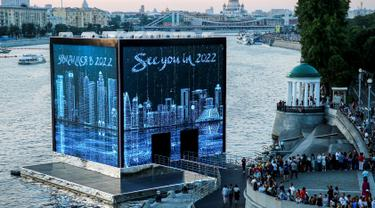 Warga melihat ke Majlis Qatar yang menyajikan pertunjukan cahaya di Gorky Park, Moskow, Rusia, Kamis (12/7). Qatar akan menjadi tuan rumah Piala Dunia 2022. (Maxim ZMEYEV/AFP)