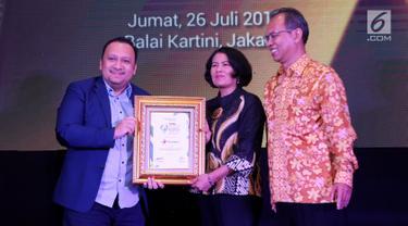 Sekjen Kementerian Kominfo Niken Widiastuti (kedua kanan) memberikan penghargaan kepada Senior Vice President Enterprise Account Management TelkomselDharma Simorangkir(kiri) dalam ajang Most Innovative Business Award 2019 di Jakarta, Jumat (26/7/2019). (Liputan6.com/HO/Ady)