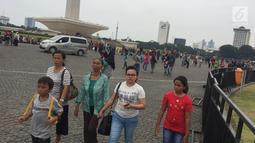 Sejumlah pengunjung menikmati suasana kawasan Silang Monumen Nasional (Monas), Jakarta, Sabtu (30/12). Monumen setinggi 132 meter tersebut tak pernah sepi dari pengunjung, apalagi bila menjelang tahun baru. (Liputan6.com/Immanuel Antonius)