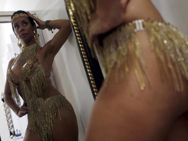 """Seorang penari karnaval atau orang Brasil menyebutnya """"muses"""", Larissa Neto saat mencoba kostum didepan kaca untuk memeriahkan karnava di Brasil, (3/2). Di Brasil menjadi seorang muses merupakan impian para gadis Brasil. (REUTERS / Ricardo Moraes)"""