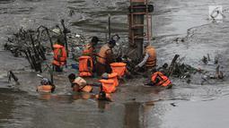Sejumlah pasukan oranye berjibaku membersihkan sampah batang kayu dan bambu yang tersangkut di aliran sungai Ciliwung di kawasan Sudirman, Jakarta, Jumat (9/2). (Liputan6.com/Faizal Fanani)