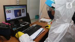 Petugas menggunakan Alat Pelindung Diri (APD) saat melayani warga yang mengajukan pembuatan KTP Elektronik di Pondok Aren, Tangerang Selatan, Senin (15/6/2020). Penggunaan APD ini bertujuan meminimalisir kontak fisik sebagai upaya pencegahan penularan Corona COVID-19. (Liputan6.com/Angga Yuniar)