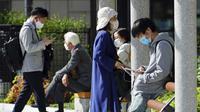 Orang-orang yang mengenakan masker pelindung untuk membantu mengekang penyebaran virus corona COVID-19 mengunjungi taman di Tokyo, Jepang, Kamis (15/4/2021). Tokyo mengonfirmasi lebih dari 700 kasus baru COVID-19 pada 15 April 2021. (AP Photo/Eugene Hoshiko)