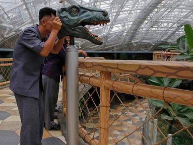 Seorang pria melihat melalui perangkat untuk mempelajari visi dinosaurus di Kebun Binatang di Pyongyang, Korea Utara (15/9). Kebun binatang nasional Korea Utara ini  terletak dekat Mt. Taesong di pusat kota Pyongyang. (AP Photo/Kin Cheung)