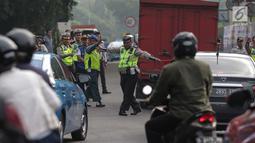 Petugas polisi lalu lintas memberhentikan kendaraan saat pemberlakuan sistem ganjil genap di pintu masuk Gardu Tol Cibubur 2, Jakarta, Senin (16/4). Kebijakan ini diterapkan untuk mengurai kemacetan di ruas Tol Jagorawi. (Liputan6.com/Faizal Fanani)