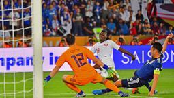 Striker Qatar, Almoez Ali, berusaha membobol gawang kiper Jepang, Shuichi Gonda, pada laga final Piala Asia 2019 di Stadion Zayed Sports City, Abu Dhabi, Jumat (1/2). Qatar menang 3-1 atas Jepang. (AFP/Giuseppe Cacace)