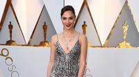 Aktris Gal Gadot berpose untuk fotografer di karpet merah Piala Oscar 2018 di Dolby Theatre, Los Angeles, Minggu (4/3). Gaun Gal Gadot hadir dengan rok model fringe yang merupakan koleksi rumah mode Givenchy. (Jordan Strauss/Invision/AP)