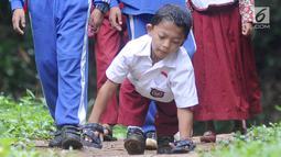 Mukhlis Abdul Holik (8) menuju sekolahnya di Kampung Cikiwul Tonggoh, Sekarwangi, Sukabumi, Kamis (15/11). Dengan penuh semangat dan percaya diri, bocah 8 tahun ini sehari-hari harus merangkak sejauh 3 km menuju SDN 10 Cibadak. (Merdeka.com/Arie Basuki)