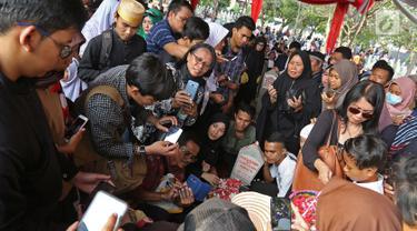 Sejumlah warga memadati pusara mendiang Presiden ketiga BJ Habibie di Taman Makam Pahlawan Nasional Kalibata, Jakarta, Kamis (12/9/2019). Mereka mengantre untuk berfoto maupun berdoa di depan makam BJ Habibie. (Liputan6.com/Herman Zakharia)