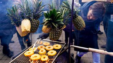 Seorang pria memanggang irisan nanas saat Riga Street Food Festival di Riga, Latvia, Sabtu (18/1/2020). Api unggun dan kios-kios makanan didirikan di sudut Jalan Kalku dan Valnu di Kota Tua Riga agar pengunjung dapat menikmati berbagai hidangan populer dari kota tersebut. (Xinhua/Janis)