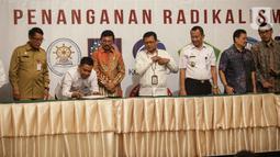 Menkominfo Johnny G. Plate (ketiga kiri) bersama sebelas Kementerian dan lembaga negara  saat penandatangan kerja sama pembuatan portal aduan untuk aparatur sipil negara (ASN), Jakarta, Selasa (12/11/2019). Portal ini bisa melaporkan ASN yang diduga terpapar radikalisme. (Liputan6.com/Faizal Fanani)