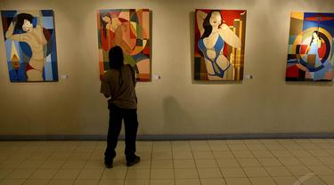 Seorang pengunjung memperhatikan lukisan karya RB Ali di Galeri Cipta 3, TIM, Jakarta, (6/10/14). (Liputan6.com/Faizal Fanani)