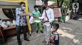 Warga menerima sembako usai mengikuti vaksinasi COVID-19 di Kantor Kelurahan Ancol, Jakarta, Kamis (17/6/2021). LMK Kelurahan Ancol membagikan sembako secara gratis kepada peserta vaksinasi COVID-19. (merdeka.com/Iqbal S. Nugroho)