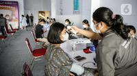 Petugas memeriksa suhu tubuh pekerja swasta saat program Vaksinasi Gotong Royong di Sudirman Park Mall, Jakarta, Rabu (19/5/2021). Vaksinasi Gotong Royong memfasilitasi badan usaha yang mau membeli vaksin untuk karyawannya. (Liputan6.com/Faizal Fanani)