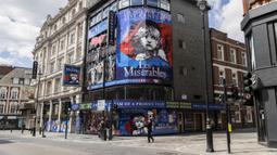 Seorang pria yang mengenakan masker berjalan melewati teater yang tutup di London, Inggris, 12 Mei 2020. Sedikitnya 5.000 pekerja teater di Inggris kehilangan pekerjaan selama diberlakukannya kebijakan penutupan (shutdown) akibat merebaknya COVID-19. (Xinhua/Han Yan)
