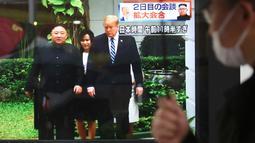 Pejalan kaki melihat layar TV siaran langsung pertemuan Presiden AS Donald Trump dan pemimpin Korut Kim Jong Un di Tokyo, Jepang (28/2). Dalam pertemuan tersebut Trump dan Kim membahas perundingan terkait nuklir. (AP Photo/Koji Sasahara)