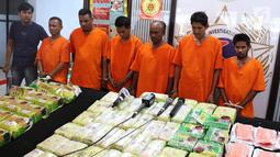 Tersangka beserta barang bukti kasus narkotika jaringan Malaysia-Sumatera saat rilis di Jakarta, Senin (4/2). Polisi menyita 16 Kg sabu, 50 Kg kristal putih, 15 ribu butir pil ekstasi, sebungkus H-5, serta empat mobil. (Liputan6.com/Immanuel Antonius)