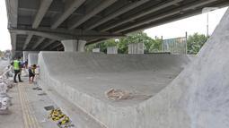 Pekerja menyelesaikan pembangunan Skate Park kolong Flyover Pasar Rebo, Jakarta, Selasa (10/12/2019). Adapun anggaran untuk pembuatan skatepark tersebut sebesar Rp14,3 miliar. (Liputan6.com/Herman Zakharia)