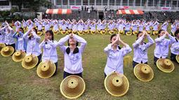 Ratusan pelajar menari saat mengikuti gladi resik di halaman sekolah di Bangkok, Thailand (13/11/2019). Gladi resik diadakan sebagai persiapan untuk kunjungan Paus Fransiskus yang  akan berada di Thailand pada 20-23 November 2019. (AFP Photo/Chalinee Thirasupa)