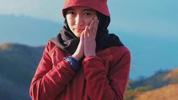 Saat mendaki Gunung Prau, gadis yang berusia 22 tahun ini tidak lupa untuk berfoto dengan pemandangan indah pegunungan. Gayanya tampak imut dengan jaket berwarna merah dan topi dengan warna senada. (Liputan6.com/IG/@arafahrianti)
