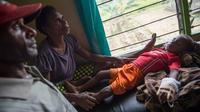 Sepasang suami istri menemani anak mereka yang sedang dirawat di klinik setempat di desa Ayam distrik Asmat, di provinsi Papua Barat (26/1). Jumlah tersebut terhitung sejak September 2017 hingga 24 Januari 2018. (AFP/Bay Ismoyo)