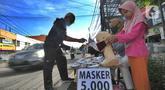 Seorang ibu ditemani anaknya melayani pembeli saat berjualan masker kain buatan rumahan di Jalan Raya Cinere-Depok, Limo, Depok, Rabu (8/4/2020).  Anjuran pemerintah mengenai penggunaan masker kain dimanfaatkan ibu ini untuk berjualan masker kain. (merdeka.com/Arie Basuki)