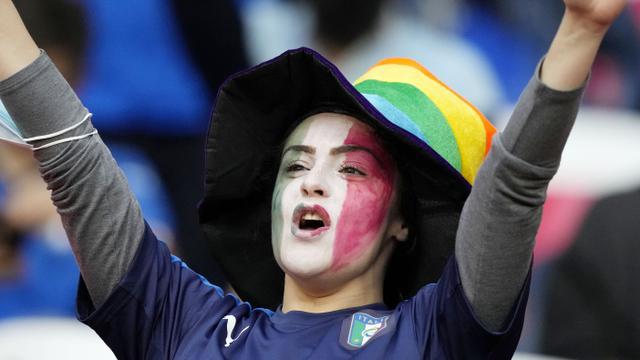 Suporter Timnas Italia mencat wajahnya dengan warna bendera nasionalnya saat menyaksikan pertandingan melawan Spanyol pada laga semifinal Euro 2020 di Stadion Wembley, Rabu (7/7/2021). (Foto:AP/Frank Augstein,Pool)