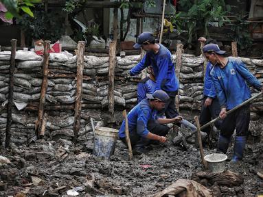 Petugas Suku Dinas SDA Jakarta Selatan membangun turap permanen di lokasi tanggul jebol di Kelurahan Jatipadang, Jakarta, Rabu (16/1). Kasudin SDA Jakarta Selatan Holi Susanto menargetkan pembangunan selesai dalam tiga minggu. (Liputan6.com/Faizal Fanani)